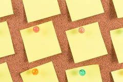 Nota pegajosa del recordatorio amarillo sobre tablero del corcho Foto de archivo libre de regalías