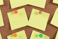 Nota pegajosa del recordatorio amarillo sobre tablero del corcho Fotos de archivo libres de regalías