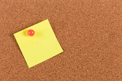 Nota pegajosa del recordatorio amarillo sobre tablero del corcho Fotografía de archivo