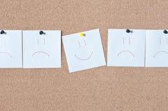 Nota pegajosa do sorriso do lembrete branco na placa da cortiça Imagem de Stock