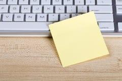 Nota pegajosa en blanco con el teclado Imagen de archivo libre de regalías