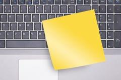 Nota pegajosa en blanco sobre el teclado Foto de archivo libre de regalías