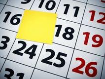 Nota pegajosa en blanco sobre un calendario Fotos de archivo