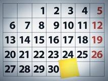 Nota pegajosa en blanco sobre un calendario Imagen de archivo libre de regalías