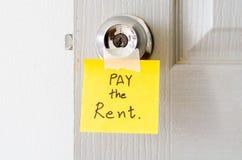 A nota pegajosa escreve a um pagamento da mensagem o aluguel Fotos de Stock