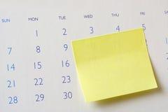 Nota pegajosa sobre calendario Fotos de archivo