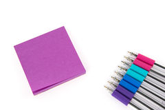 Nota pegajosa vazia cor-de-rosa no fundo branco com penas coloridas Fotografia de Stock Royalty Free