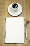 Nota, pen en kop van koffie Stock Foto's