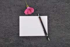 Nota, pluma y malva en pizarra foto de archivo libre de regalías