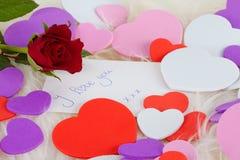 Nota romántica: Quiero con la rosa y los corazones del rojo Imagenes de archivo