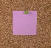 Nota roxa na placa da cortiça Imagem de Stock