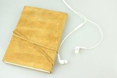 Nota y auriculares en un fondo blanco Imagen de archivo