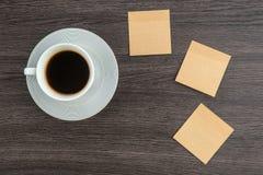 Nota y café adhesivos en el escritorio Fotos de archivo libres de regalías