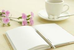 Nota y té en el escritorio foto de archivo