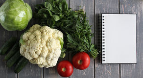 Notaboek en samenstelling van groenten op grijs houten bureau Stock Afbeeldingen