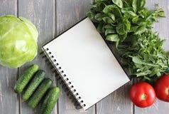 Notaboek en samenstelling van groenten op grijs houten bureau Stock Foto
