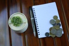 notaboek, pen, muntstukken en decoratie op houten achtergrond wordt geïsoleerd die stock afbeelding