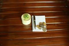notaboek, pen, muntstukken en decoratie op houten achtergrond wordt geïsoleerd die stock foto's