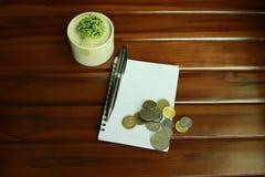 notaboek, pen, muntstukken en decoratie op houten achtergrond wordt geïsoleerd die royalty-vrije stock afbeeldingen