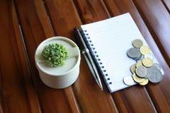 notaboek, pen, muntstukken en decoratie op houten achtergrond wordt geïsoleerd die royalty-vrije stock foto's
