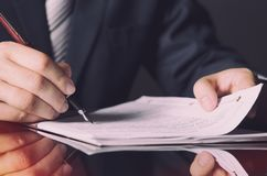 Notario que firma un contrato con la pluma en concepto del sitio oscuro imagen de archivo