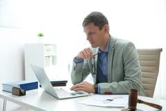 Notario que trabaja con el mazo del ordenador portátil y del juez en la tabla en oficina imagenes de archivo