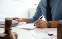 Notario que trabaja con los papeles y el mazo del juez en la tabla Concepto de la ley y de la justicia fotografía de archivo libre de regalías