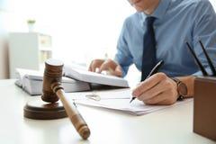Notario que trabaja con los papeles y el mazo del juez en la tabla Concepto de la ley y de la justicia fotos de archivo