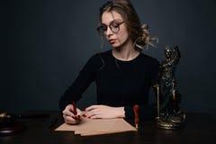 Notaris die een contract met vulpen in donker ruimteconcept ondertekenen de notaris van de de procureursadvocaat pen van de bedri stock fotografie