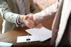 Notarius publicu och klient som i regeringsställning skakar händer, closeup royaltyfri fotografi