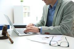 Notarius publicu som arbetar med bärbar dator- och domareauktionsklubban på tabellen Lag- och rättvisabegrepp arkivfoto