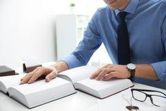 Notarius publicu som i regeringsställning studerar lagböcker på tabellen royaltyfria bilder