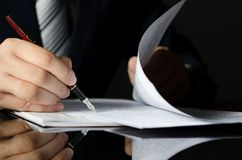 Notarius publicu som undertecknar ett avtal med reservoarpennan i mörkt rum Arkivfoto