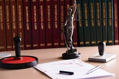 Notary public accessories. Themis with scales of justice and notarial acts in the background stock photography