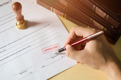 Notary signing a contract with fountain pen. Red Approved stamp. business man law attorney lawyer notary public Stock Photos
