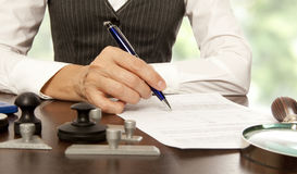 Notary signs the documents in office. Woman notary, lawyer signs the documents in office royalty free stock photo