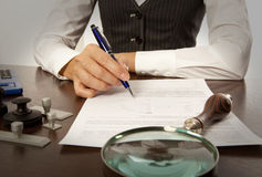 Notary signs the documents in office. Woman notary, lawyer signs the documents in office royalty free stock images