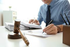 Notary working with papers and judge gavel on table. Law and justice concept stock photos