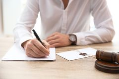 Notary working with papers and judge gavel on table in office, closeup. Law and justice concept stock photos