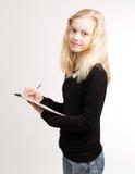 Notas adolescentes rubias de la escritura de la muchacha sobre la libreta Imagen de archivo libre de regalías