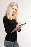 Notas adolescentes rubias de la escritura de la muchacha sobre la libreta Foto de archivo