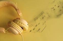 Notas amarelas dos auriculares e da música Imagem de Stock Royalty Free
