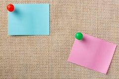 Notas azules y rosadas de la etiqueta engomada con los pernos del empuje en fondo de la lona Fotos de archivo