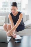 Notas bonitas da escrita da mulher de negócios ao usar o portátil no sofá Imagens de Stock Royalty Free