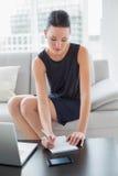 Notas bonitas da escrita da mulher de negócios pelo portátil no sofá Imagem de Stock