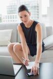 Notas bonitas da escrita da mulher de negócios pelo portátil no sofá Fotografia de Stock Royalty Free