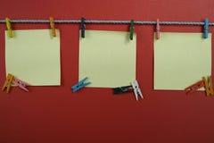 Notas coloridas em pregadores de roupa, espaço da cópia Imagem de Stock