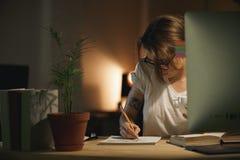 Notas concentradas de la escritura del diseñador de la mujer joven usando el ordenador Fotografía de archivo