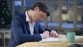 Notas da escrita do indivíduo que sentam-se na mesa vídeos de arquivo