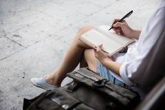 Notas da escrita da mulher no diário fotos de stock
